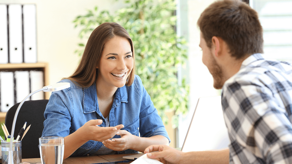 A happy woman helping a man out with paperwork